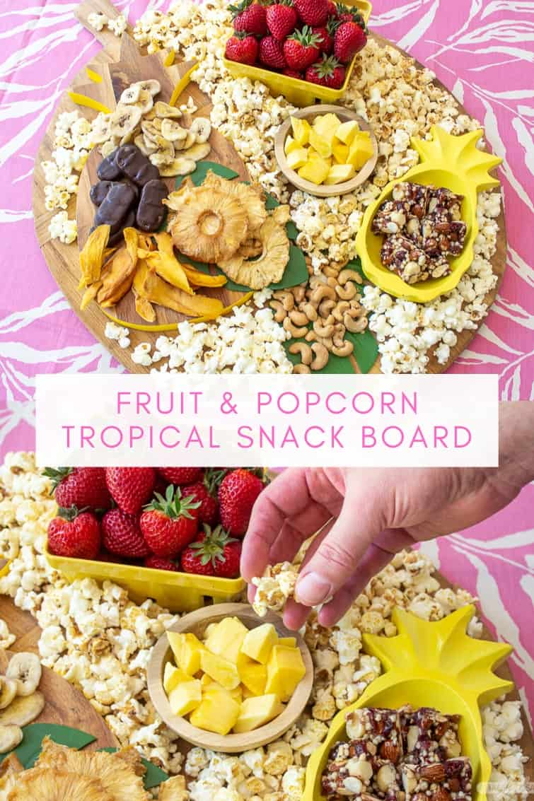 collage photo showing a man taking popcorn from a tropical charcuterie board with fruit, nuts and popcorn