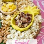 tropical charcuterie snackboard with mango, popcorn, nuts and nut clusters in a pineapple shaped bowl