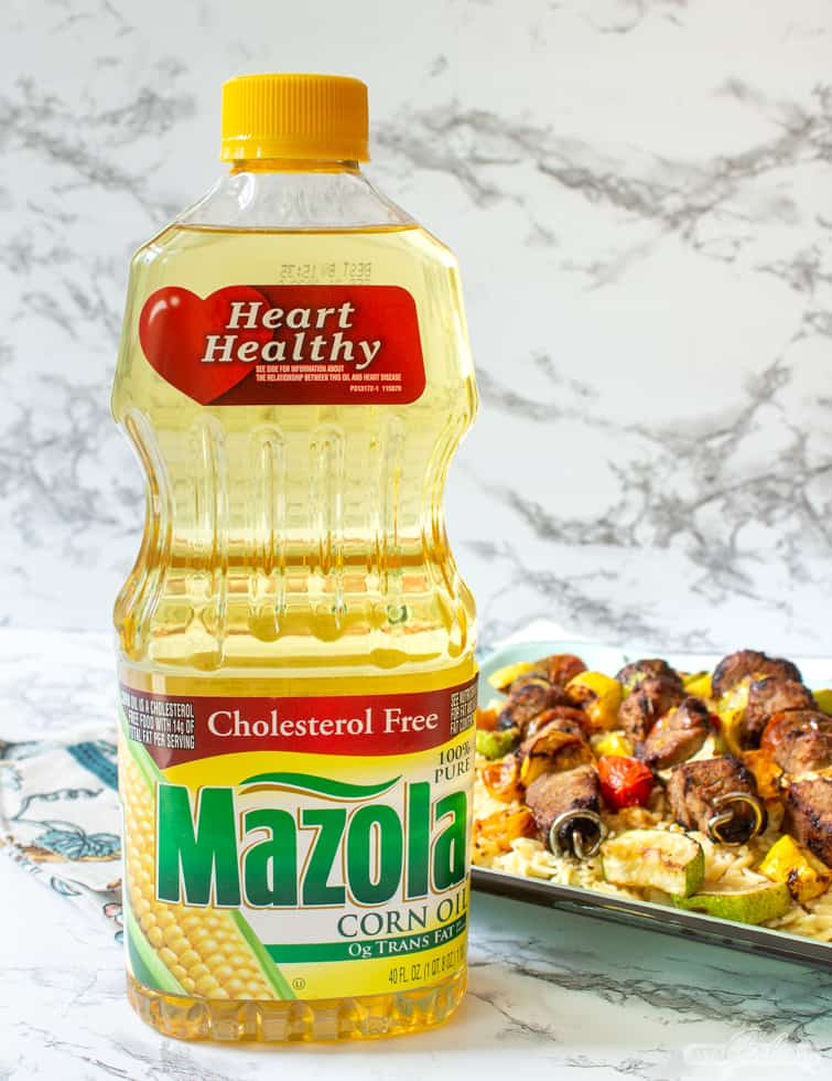 bottle of corn oil in front of a platter of pork and vegetable kabobs