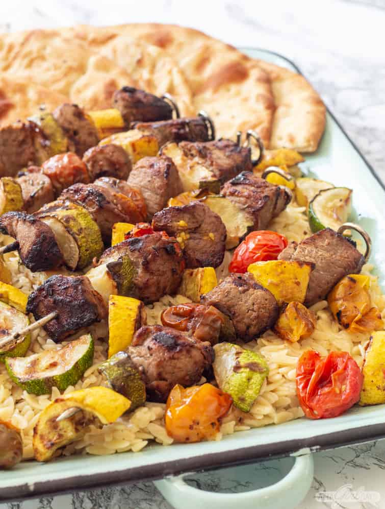 Dijon Marinated Pork Tenderloin Kabobs with Charred Vegetables over orzo on a platter