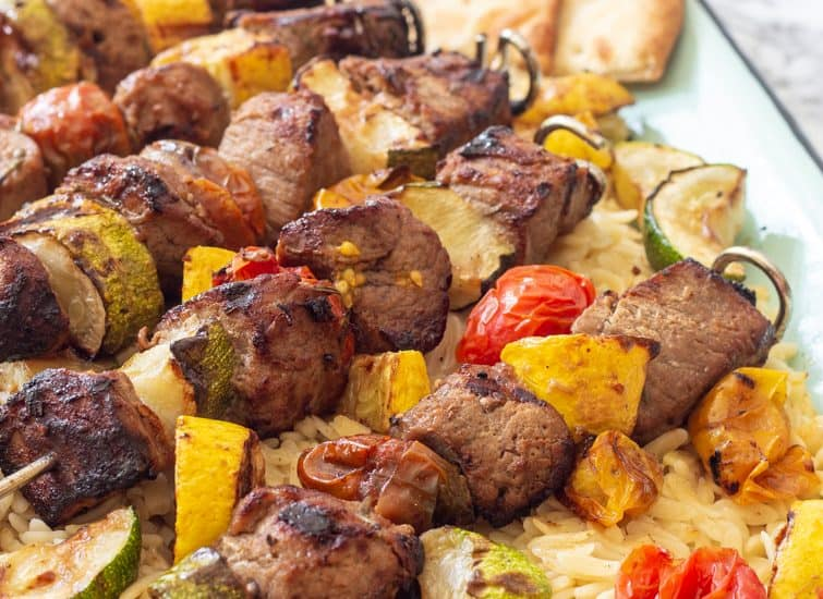 pork and vegetable kabobs over orzo pasta on an enamel tray