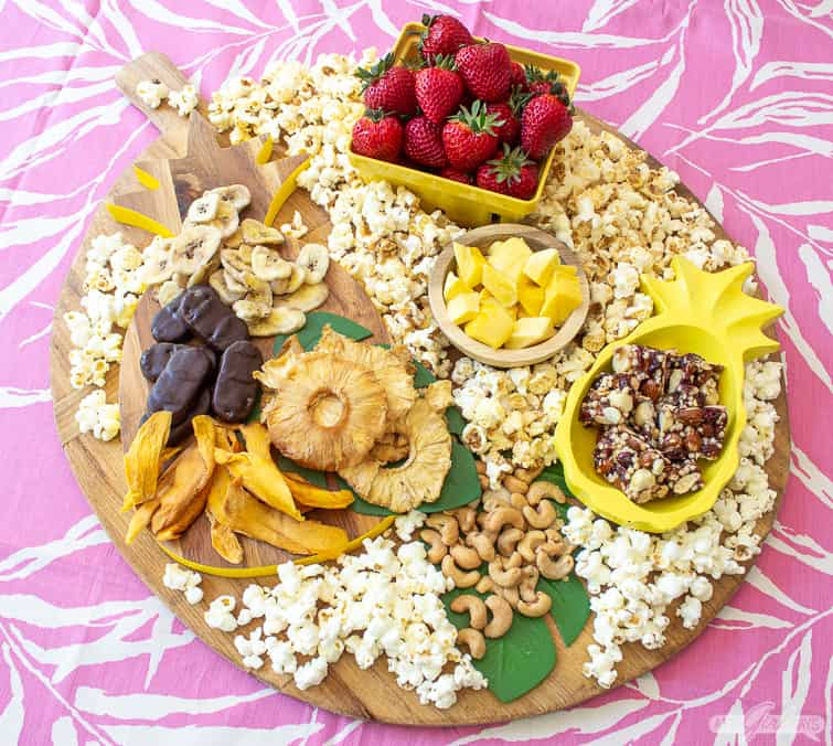 tropical charcuterie with fruit, popcorn, nuts and chocolate