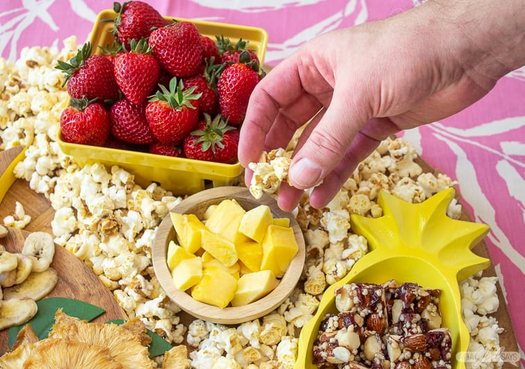 man's picking up popcorn off a tropical charcuterie board