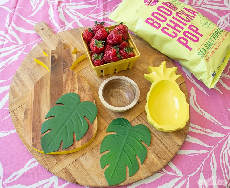 wooden snack board with strawberries, pineapple bowl and monstera leaves