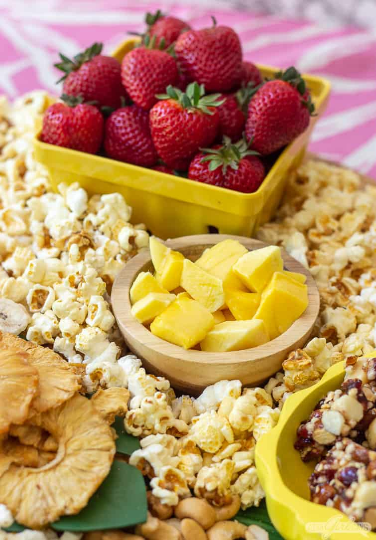 mango and strawberries and popcorn on a snack board