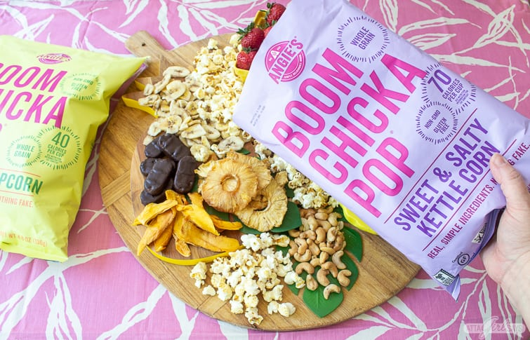 adding kettle corn to a tropical charcuterie board