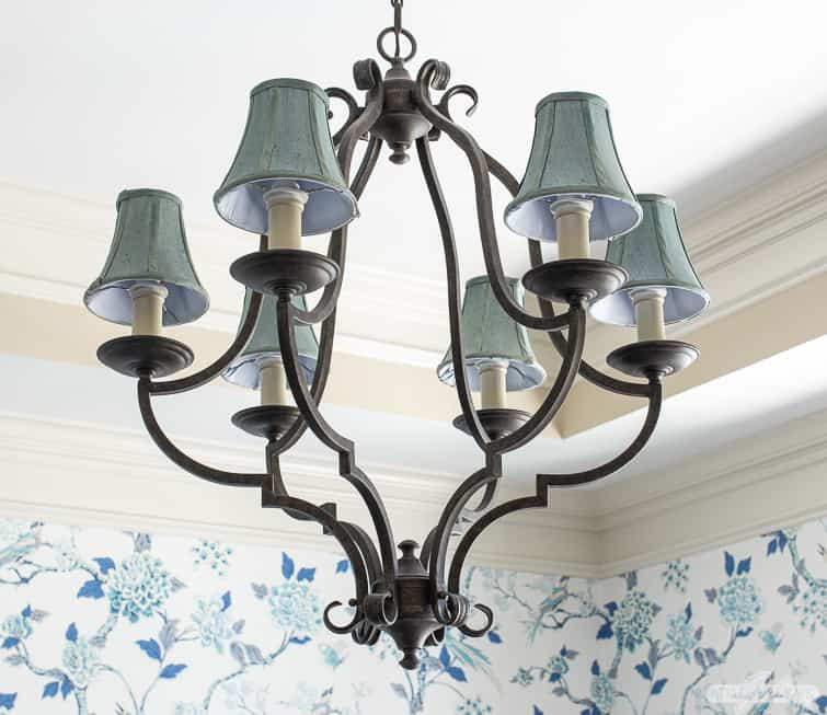 wrought iron chandelier with blue shades in a dining room with chinoiserie wallpaper