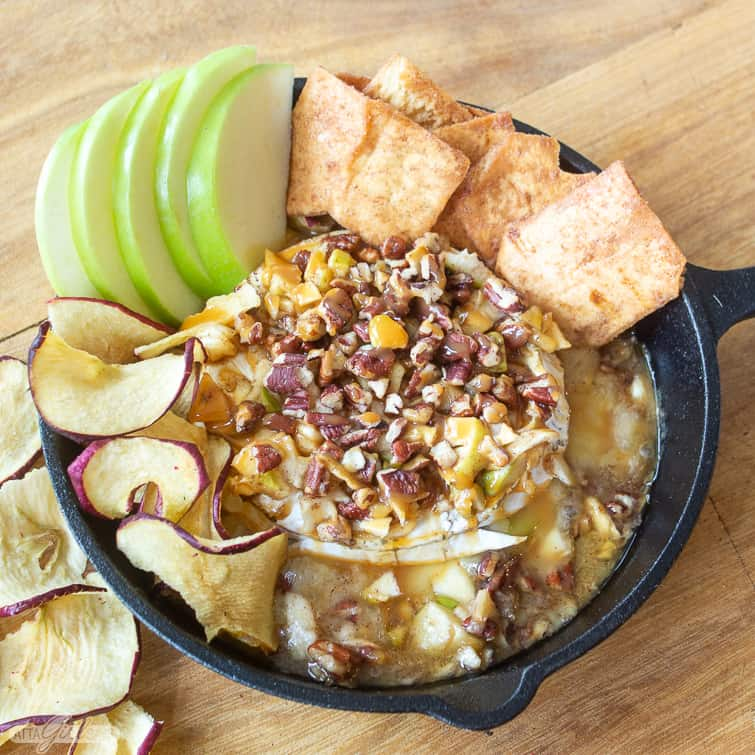baked brie with pecans, apples and caramel sauce in a cast iron skillet with apple slices and apple chips