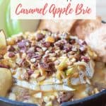 baked brie with pecans, apples and caramel sauce in a cast iron skillet