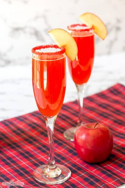 two cinnamon apple cider mimosa cocktails in champagne glasses