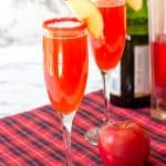 two apple cider mimosa cocktails with champagne and cinnamon vodka in the background