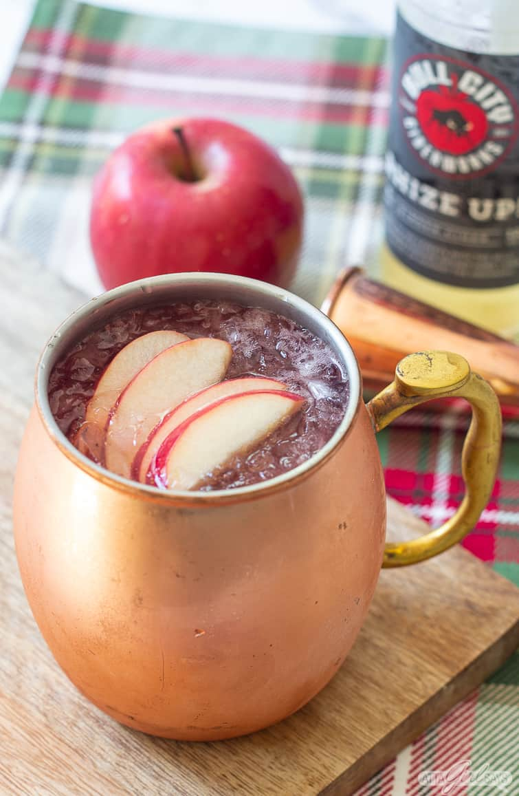 cinnamon apple cider Moscow mule garnished with apple slices in a copper mug
