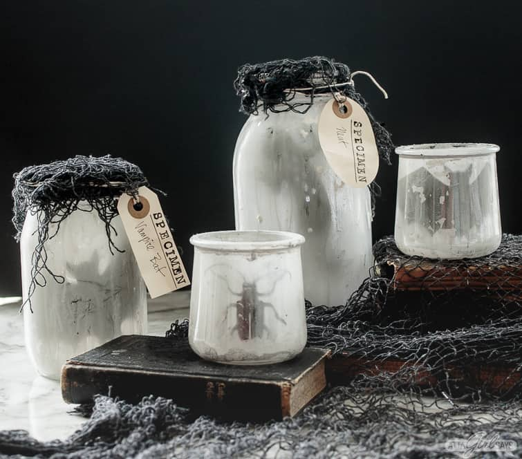 crusty Halloween specimen jars with bats, beetles and other silhouettes in them