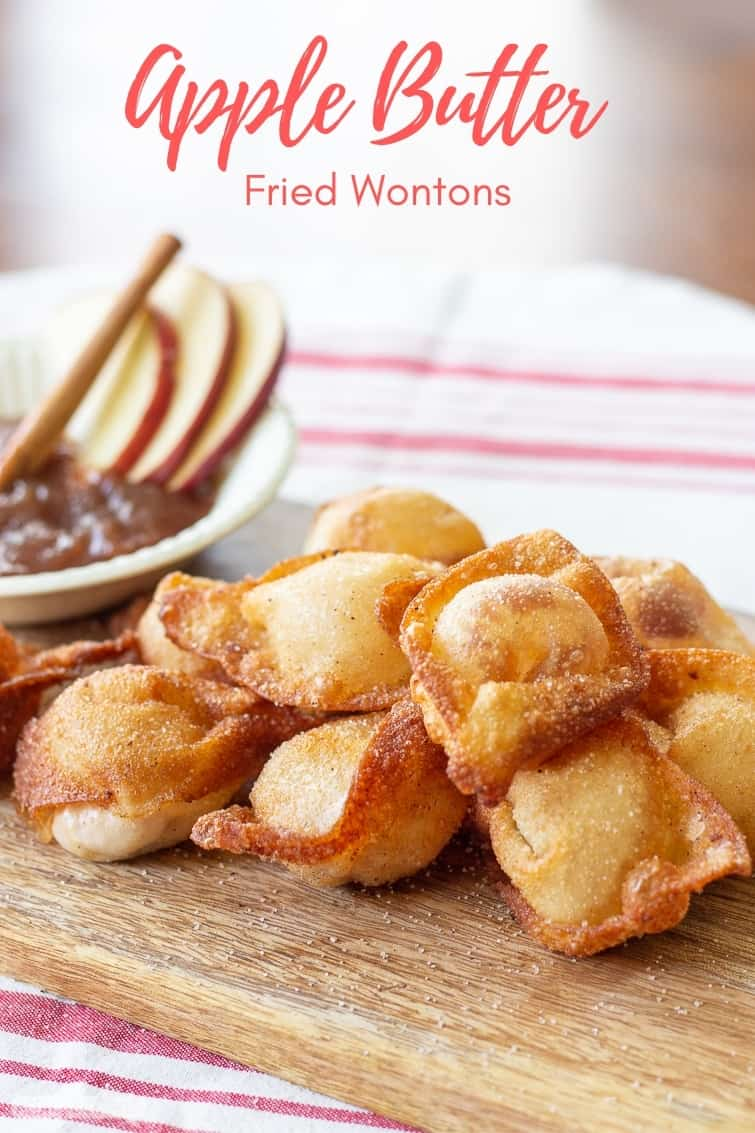 fried sweet cream cheese wontons on a wooden board with a bowl of apple butter
