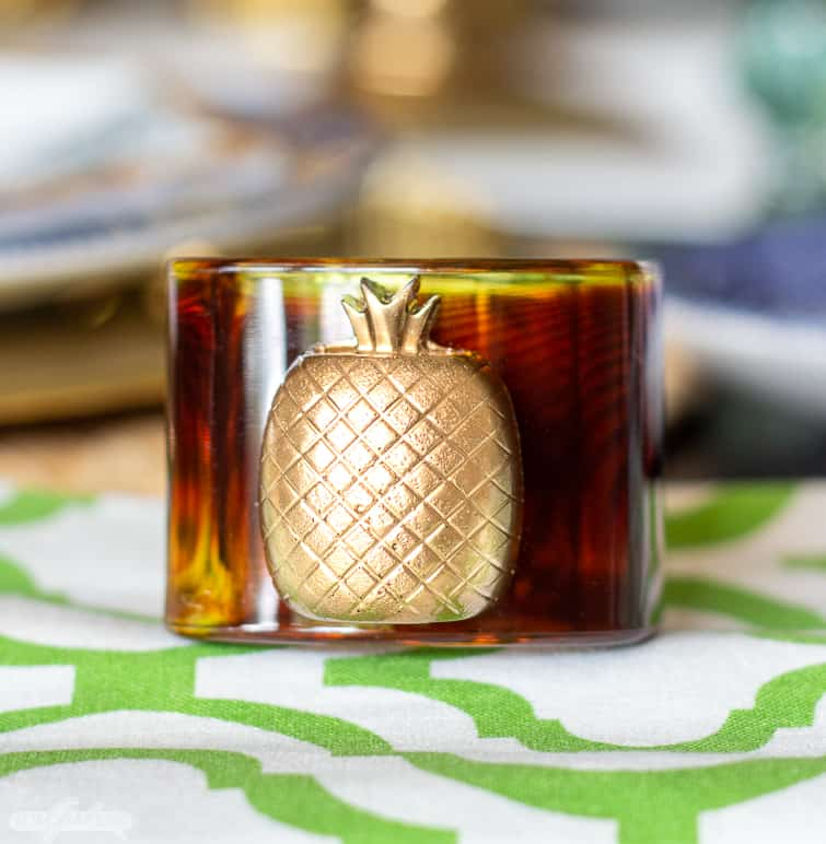 tortoise shell napkin ring with a gilded pineapple on it