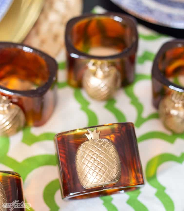 faux tortoise shell and gilded pineapple napkins rings on a green trellis napkin