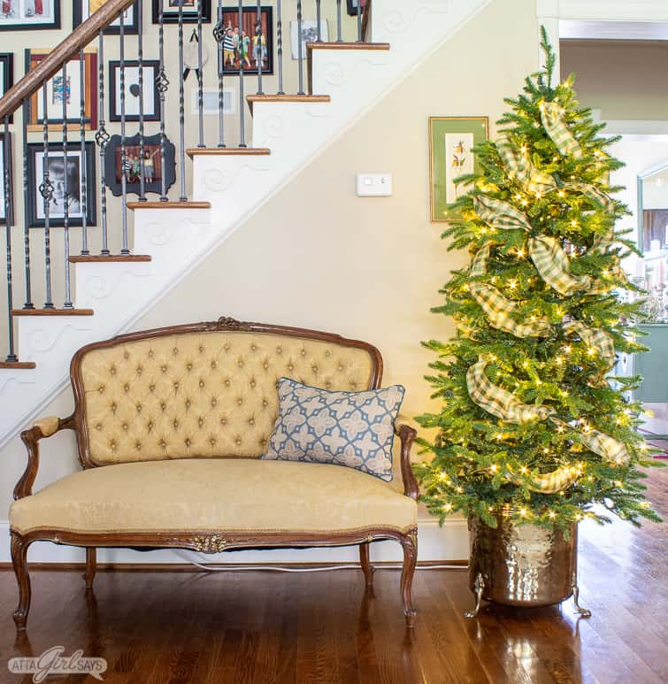 staircase with a yellow French loveseat and a Christmas tree. in a brass planter in front of it
