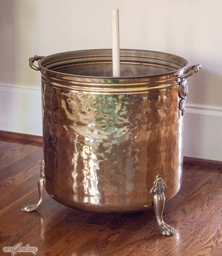 vintage brass planter with a wooden dowel rod mounted in the center