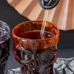 silver spider Halloween drink stirrer in an orange goblet