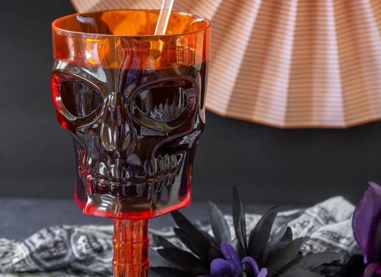 spider Halloween drink stirrers in an orange skull goblet