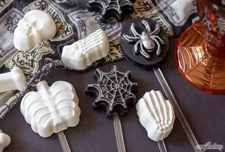 assorted Halloween cocktail stirrers on a black table