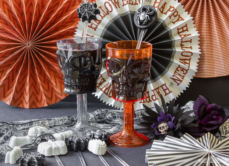 two skull goblets with Halloween cocktail stirrers sitting in front of Halloween banners