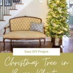 Christmas tree in a vintage brass planter beside a yellow French style settee