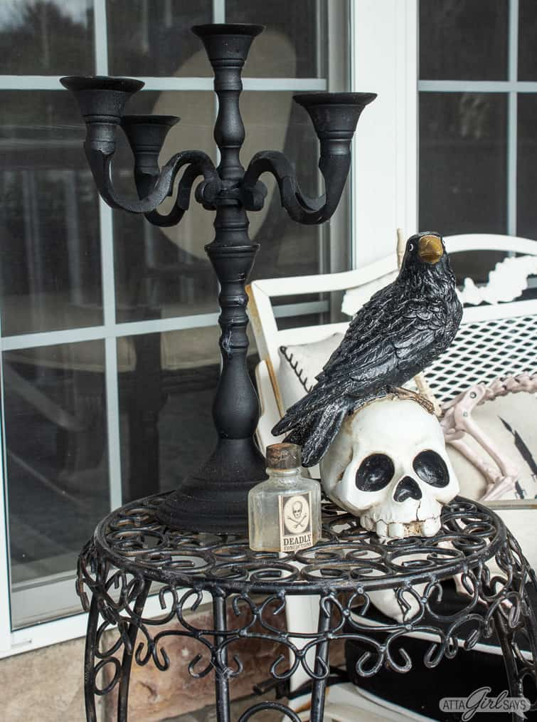 black candlabara, crow on a skull and potion bottle on a Halloween porch