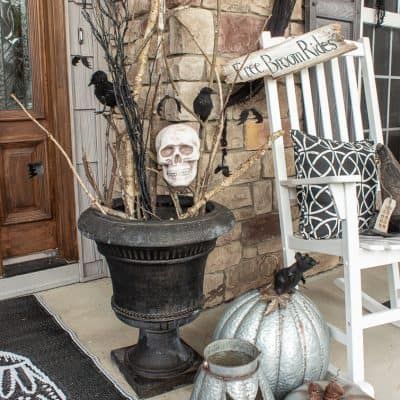 urn filled with sticks with pumpkins and skulls for Halloween