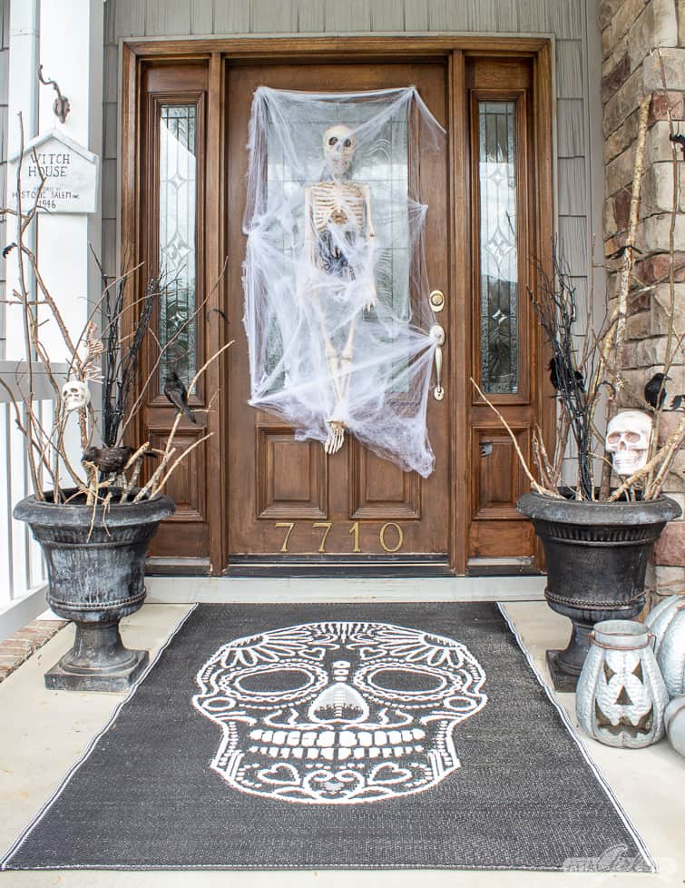 skull rug and skeleton on a front door for Halloween porch decorations