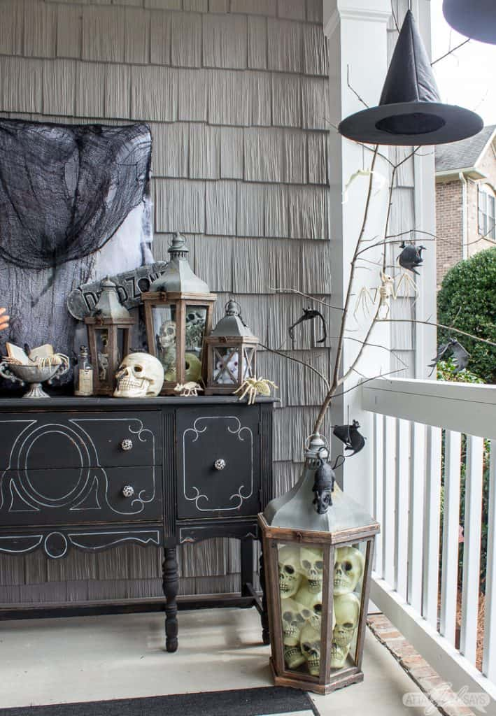 witch's hat hanging on a Halloween front porch beside a black buffet
