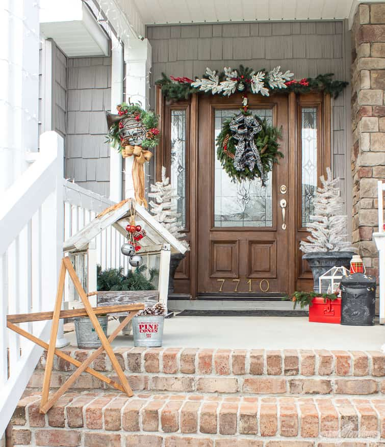 white trees in planters and a fresh evergreen wreath on the front door