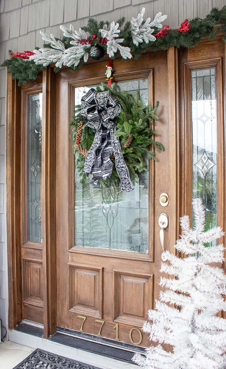 evergreen wreath with chalkboard ribbon on a wooden front door