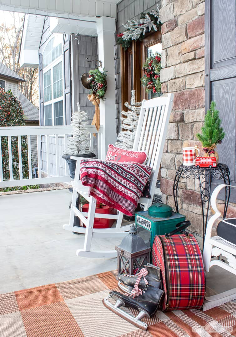 rocking chair on a porch decorated with vintage Christmas items