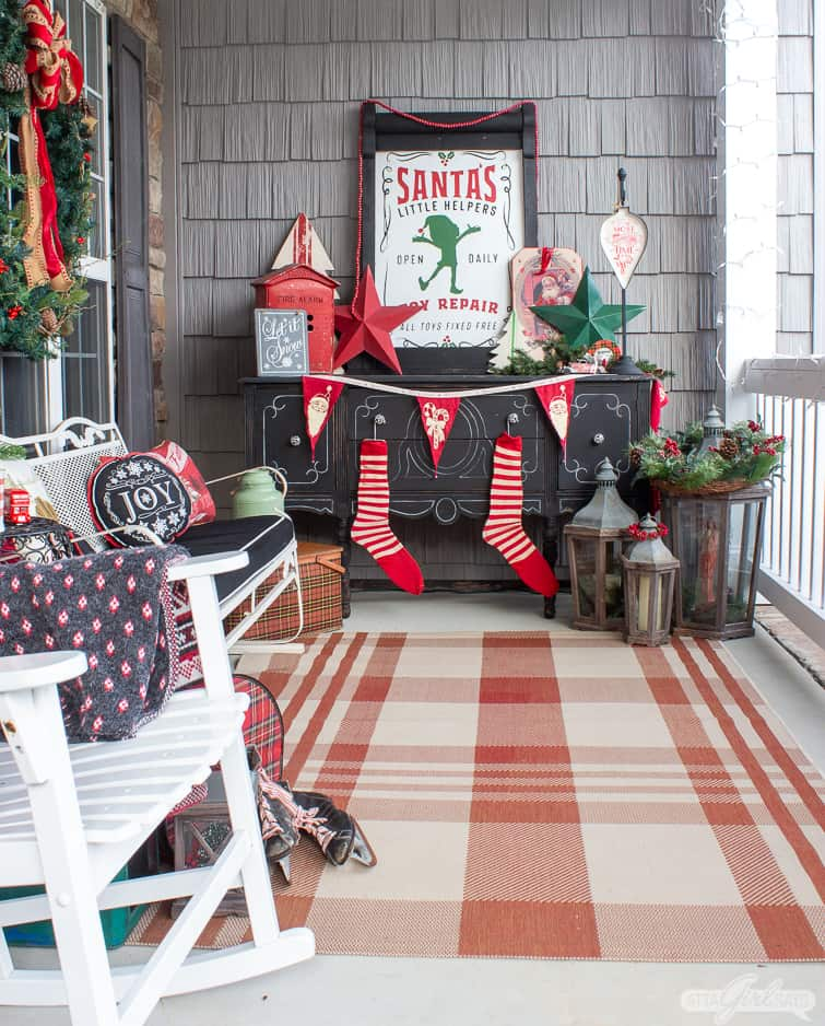 Christmas porch with a black buffet decorated with vintage items and a red and white plaid rug