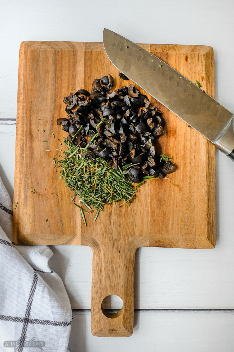 wooden cutting board with chopped herbs, capers and olives