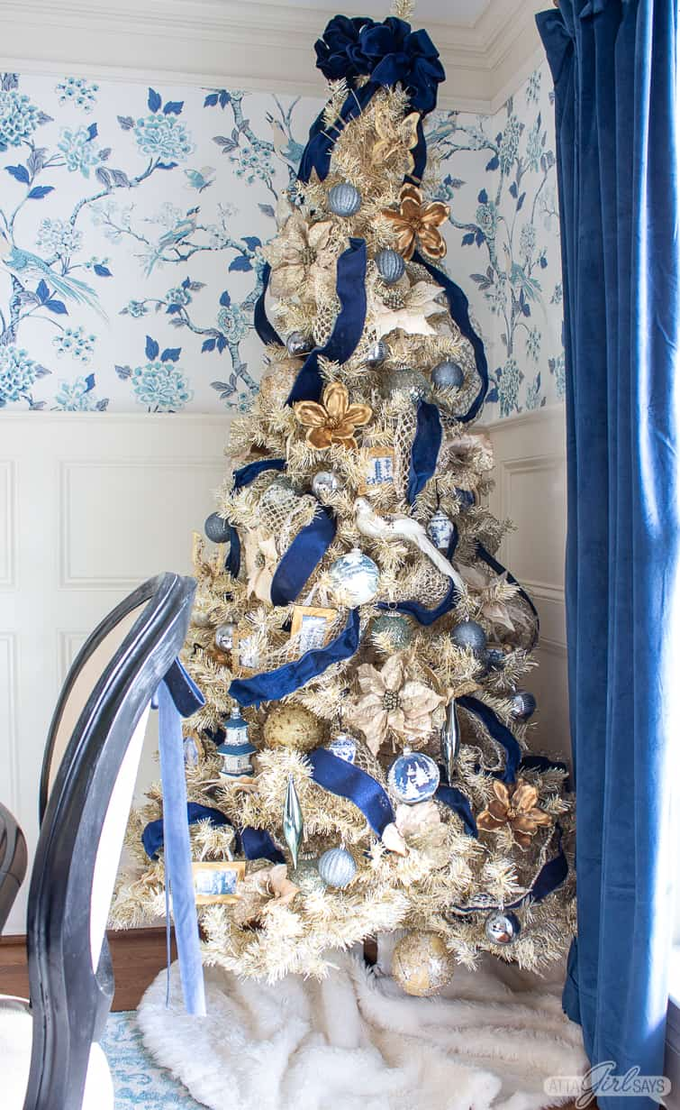 gold Christmas tree decorated with navy blue ribbon and blue and white ornaments against chinoiserie wallpaper