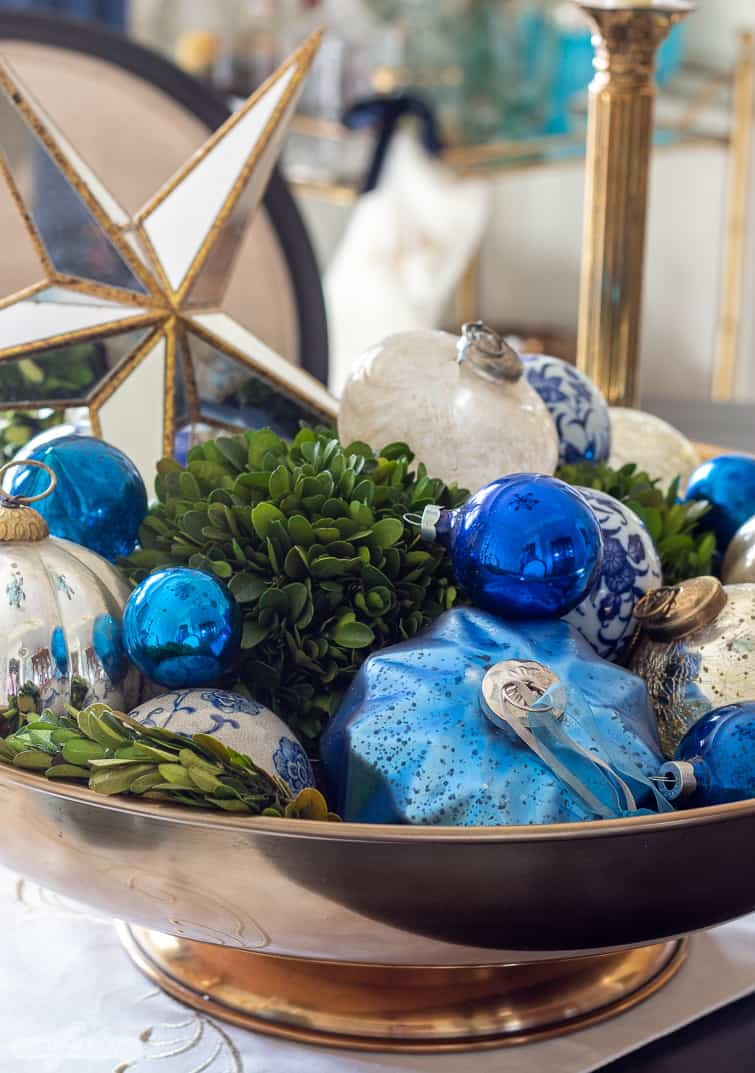 large brass centerpiece bowl filled with blue Christmas ornaments and boxwood balls on a dining room table