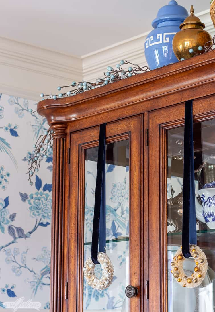 bottlebrush wreaths hanging from blue velvet ribbon on the doors of a china cabinet