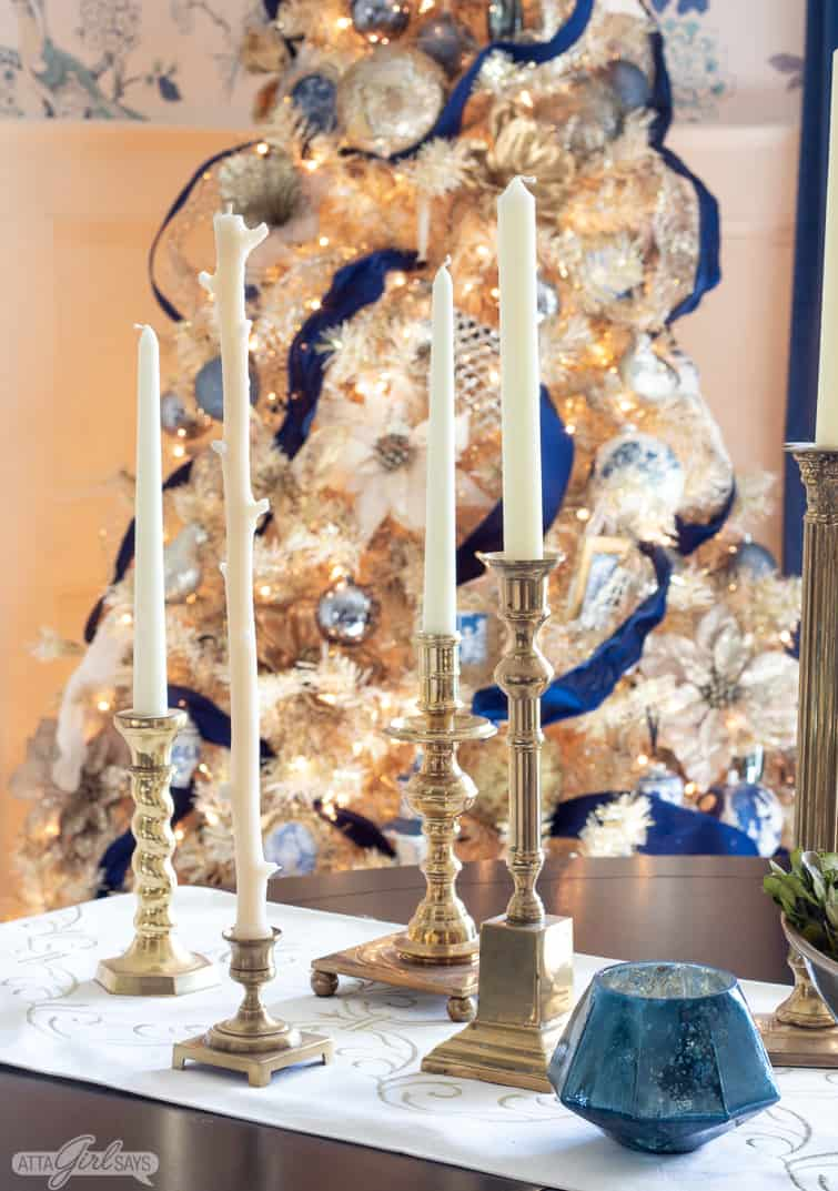 vintage brass candlesticks on a dining table with a glowing gold Christmas tree behind them