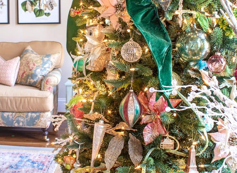 closeup of glass ornaments on a Christmas tree decorated with emerald green velvet ribbon