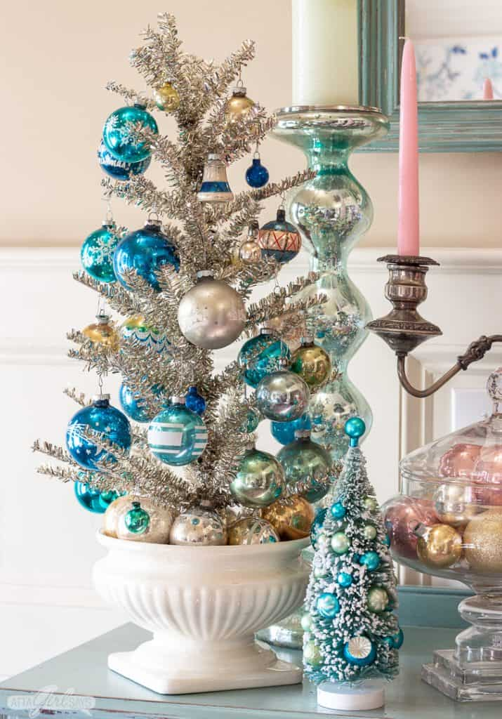 silver tinsel tree in a ceramic urn decorated with blue and aqua Shiny Brite ornaments