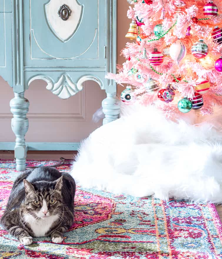tabby cat lounging in front of a pink flocked tree decorated with vintage and reproduction pink and green Shiny Brite ornaments