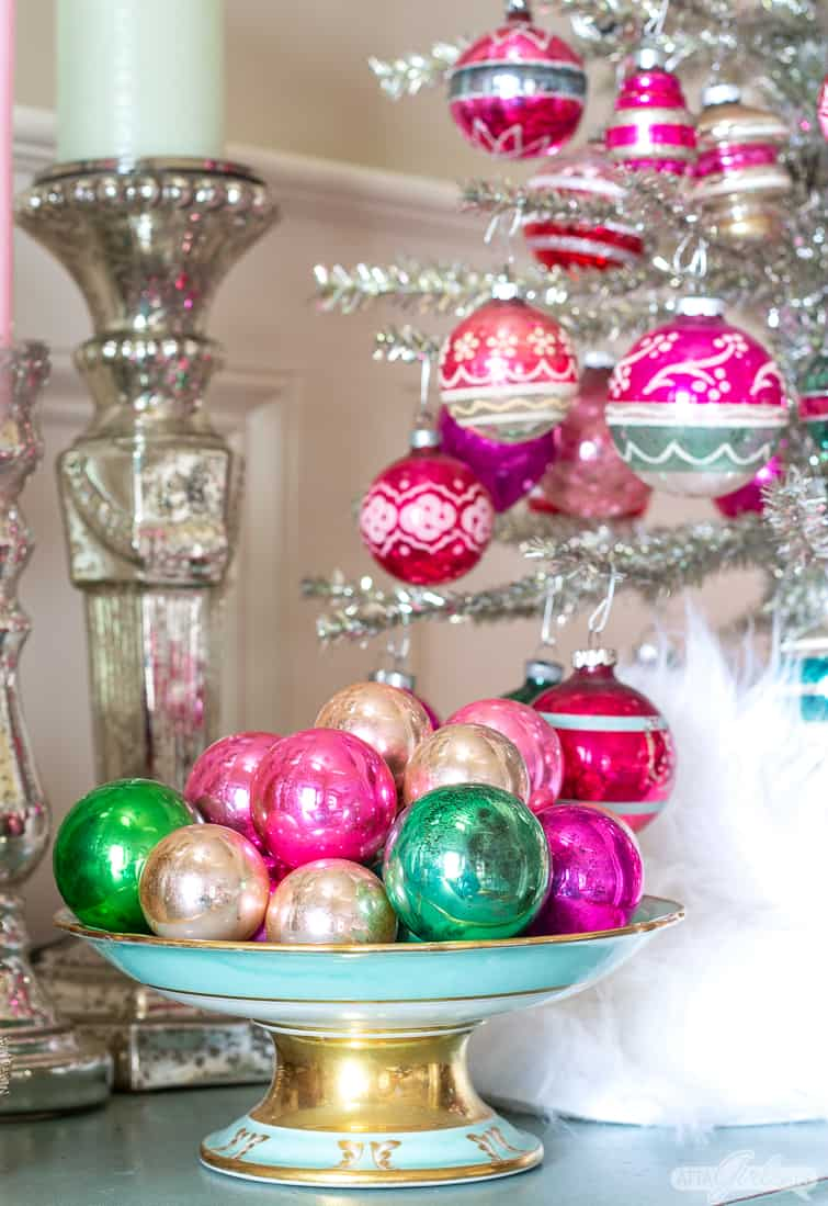 pink and green vitage ornaments in an aqua blue compote beside a tabletop tinsel tree