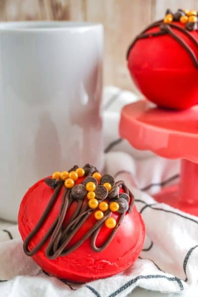white coffee mug beside a red hot candy filled with hot cocoa