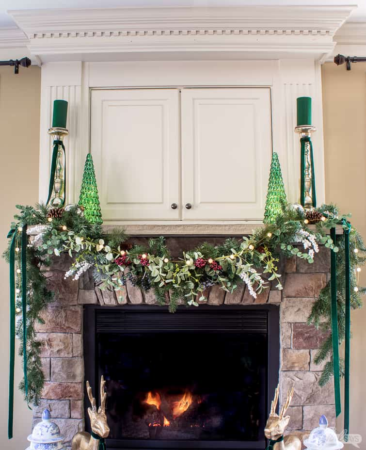 stone fireplace mantel decorated with a garland and green mercury glass trees