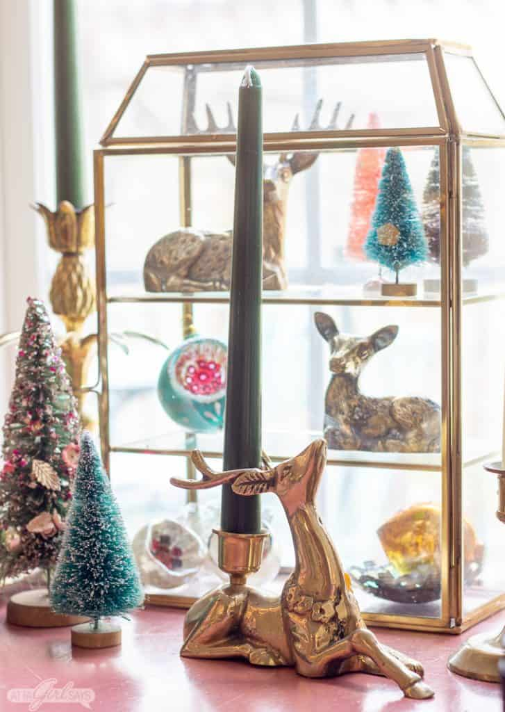 glass shadowbox filled with vintage Christmas ornaments, bottlebrush trees and brass reindeer