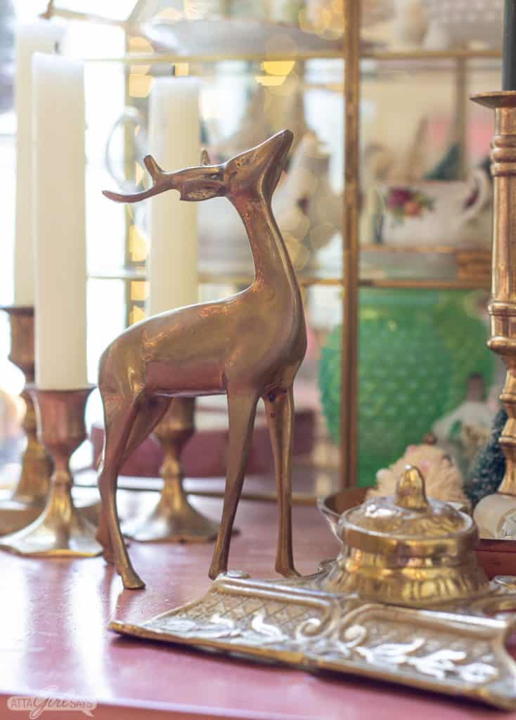 brass deer figurine in fronnt of a glass and brass shadowbox