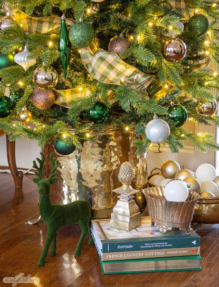 flocked deer, books and ornaments in brass containers underneath a Christmas tree in a brass planter