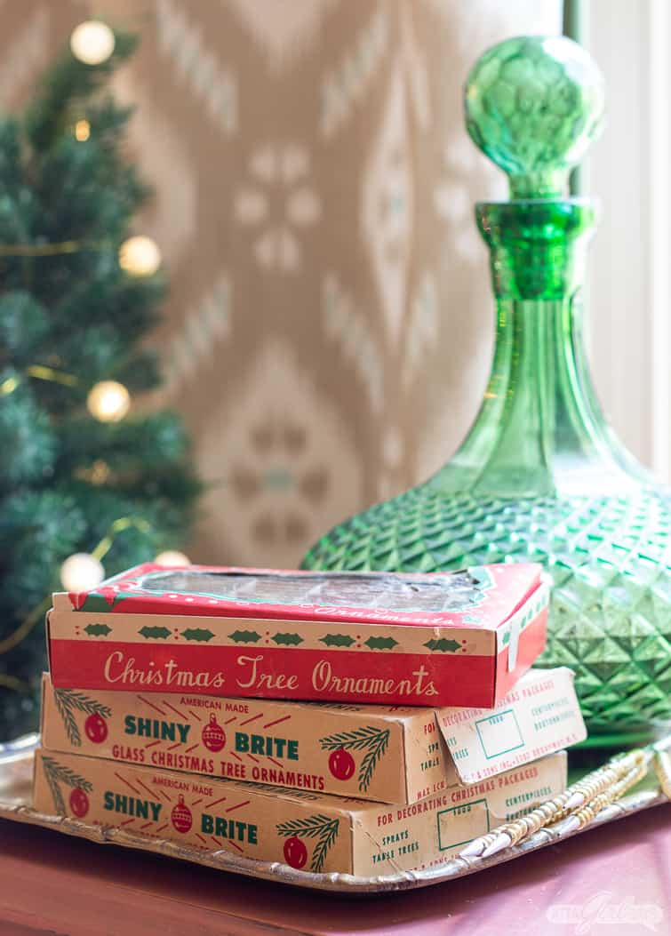 mini Shiny Brite ornament boxes stacked in front of a green glass decanter